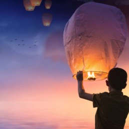 happy child setting a lantern into the night air